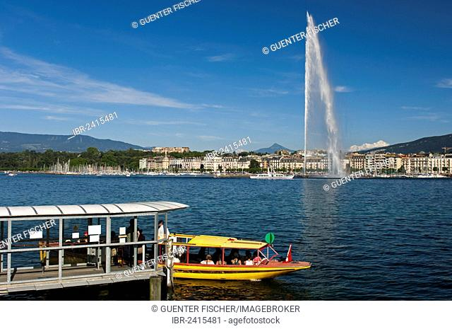 Ferry boat at the dock of the Geneva ferry company Mouettes genevoises in front of the giant fountain Jet d'Eau, with the snow-capped summit of Mont Blanc in...