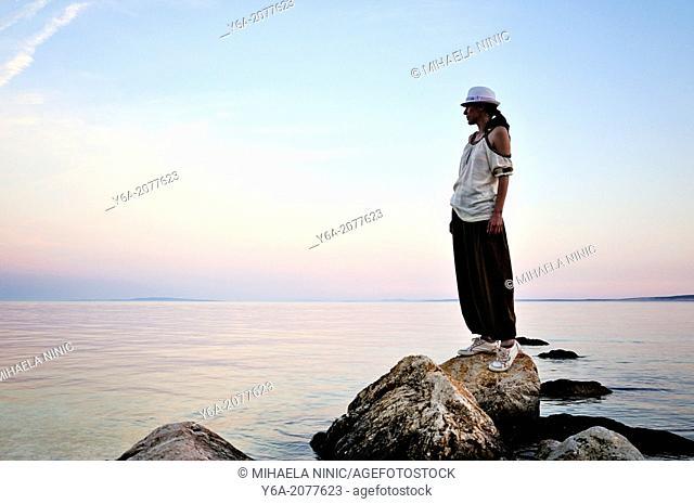 Woman standing on rock watching sunset, Island Pag, Croatia, Europe