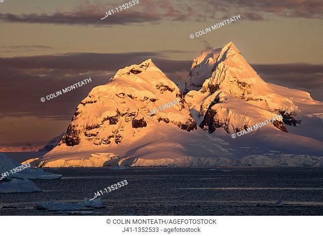 Alpenglow lights up high peaks on Wiencke Island behind Port Lockroy, Antarctic Peninsula