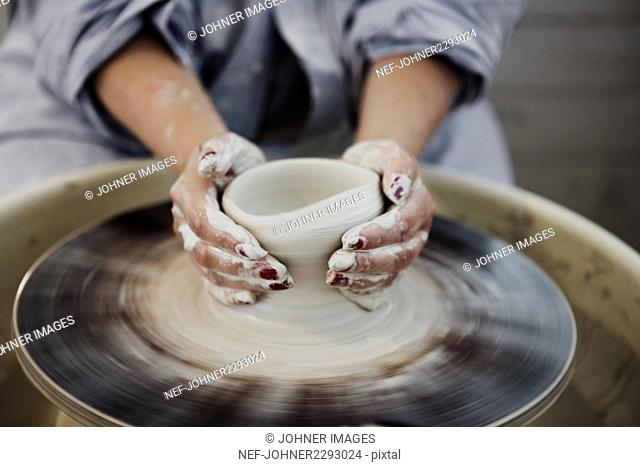 Close up of woman making pot on potters wheel
