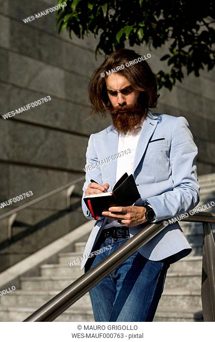 Stylish businessman writing in diary outdoors