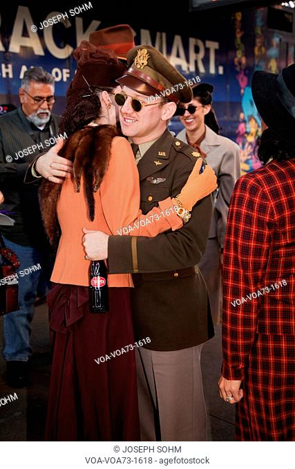 Man and woman in 1940's clothing hug during Pearl Harbor Day Troop train reenactment from Los Angeles Union Station to San Diego