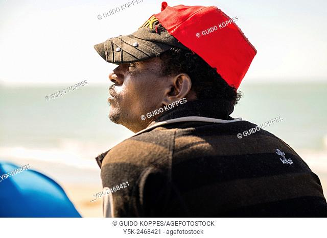 Harbor, The Jungle, Calais, France. African illegal immigrant of migrant, wearing a red cap, overlooking the Channel and the Port of Calais