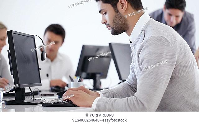Handsome ethnic businessman working on his computer and then turning and smiling confidently at the camera