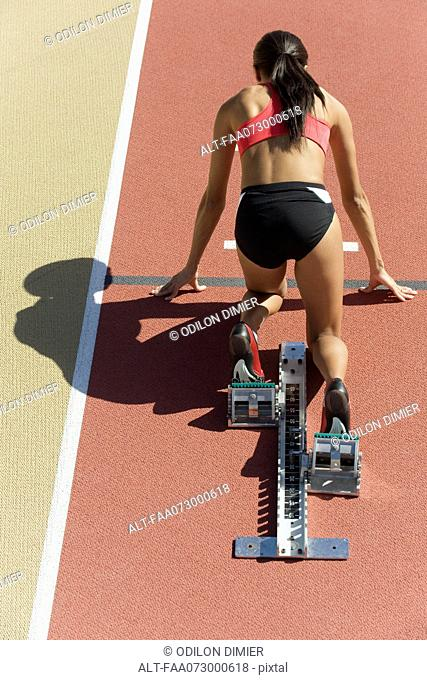 Woman crouched in starting position on running track, rear view