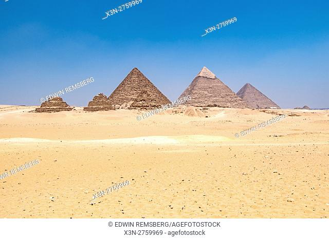 Cairo, Egypt Vast Sahara desert with the three Great pyramids of Giza in the background against a clear blue sky. From left to right stands the Pyramid of...