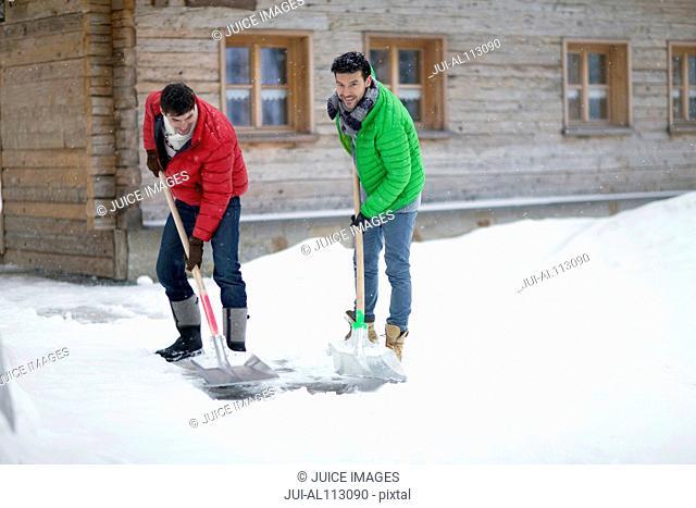 Men shoveling snow outside log cabin