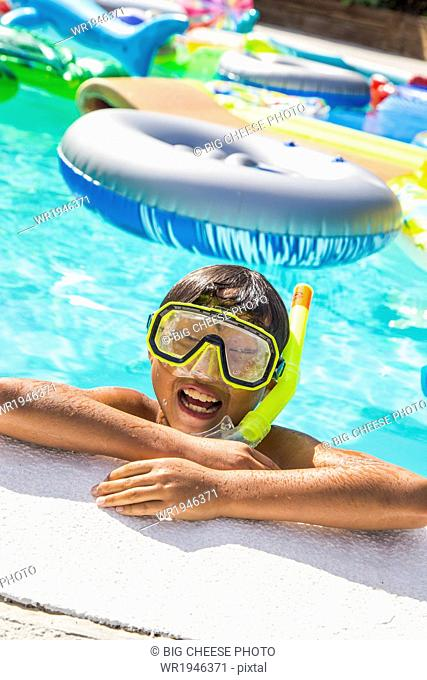 Boy wearing a scuba mask and snorkel swims in a pool full of inflatable toys
