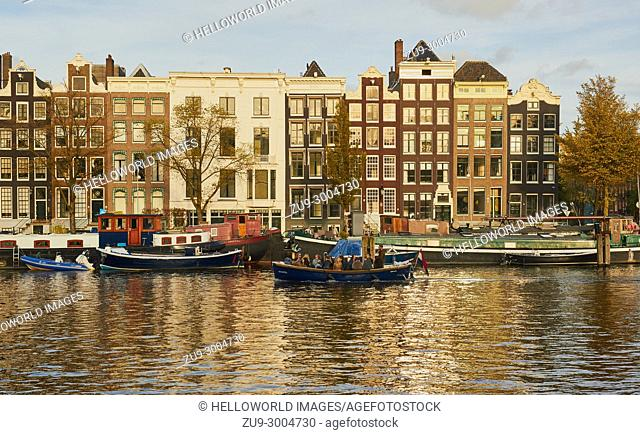 Boats and barges on the Amstel river, Amsterdam, Netherlands