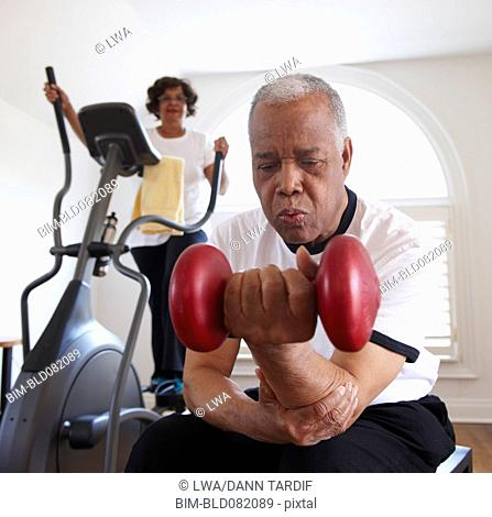 Black woman using elliptical machine, husband using hand weights