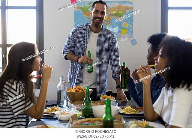 Group of friends socializing with beer and fast food at home