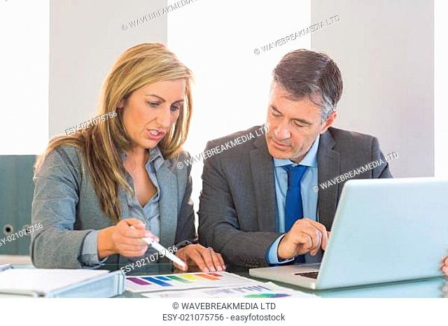 Serious businesswoman explaining figures to a concentrated businessman