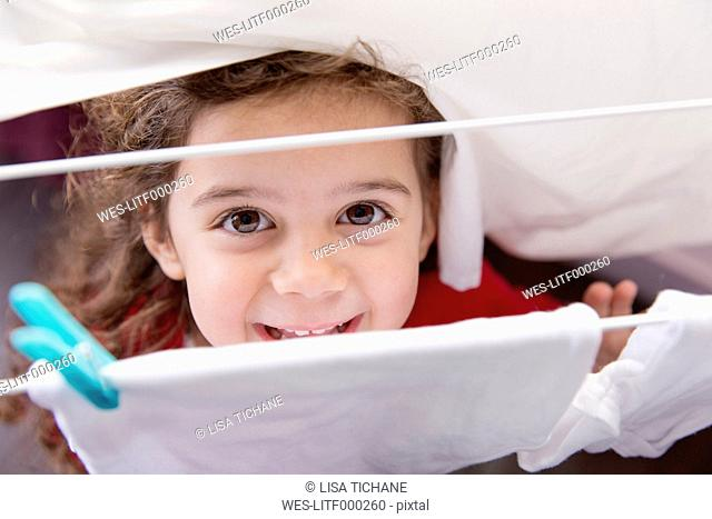 Portrait of little girl standing under a drying rack