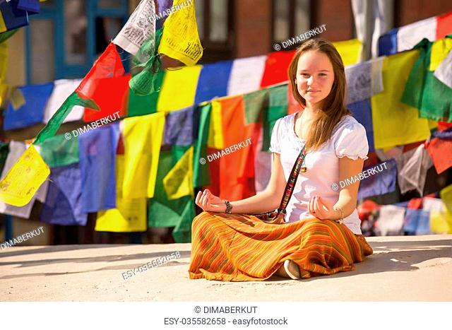 Girl sitting on Buddhist stupa, prayer flags flying in background