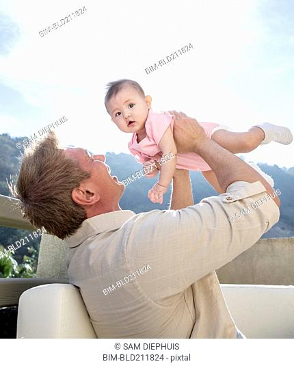 Father holding baby girl on sofa