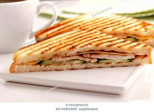 Sandwiches with chicken meat, cheese, cucumber, grilled toasts, and a cup of coffee
