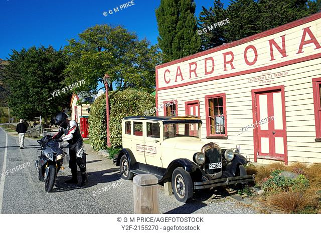 Editorial use only - historic Cardrona Hotel, antique car and modern motorcyclist near Wanaka, New Zealand