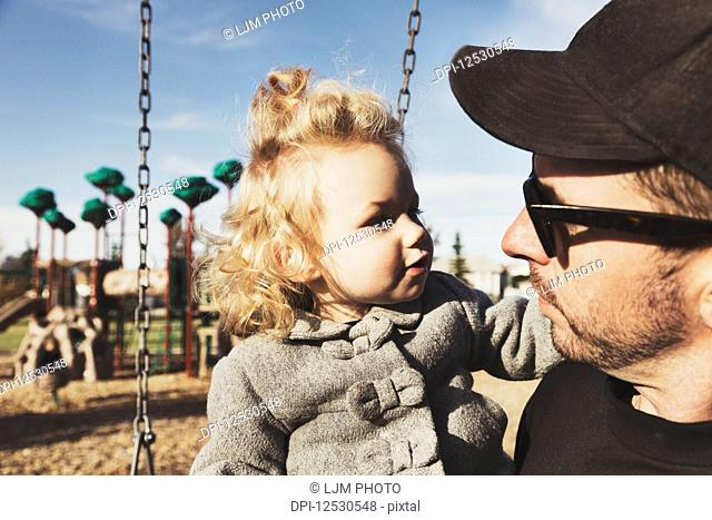 A cute young girl with her father after playing in a playground during the fall season; Spruce Grove, Alberta, Canada