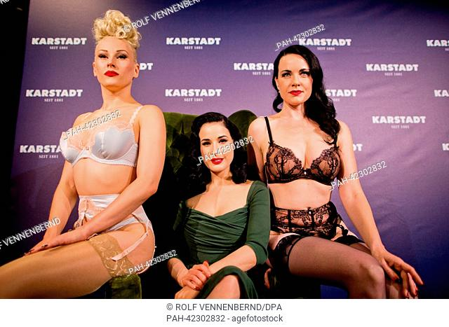 Burlesque model Dita von Teese (C) poses for the camera with two models presenting her new lingerie collection within a newly renovated Karstadt shop in...