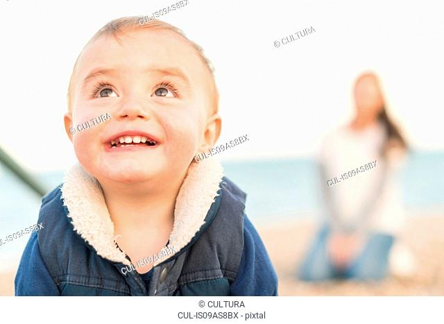 Portrait of young boy on beach with mother sitting behind