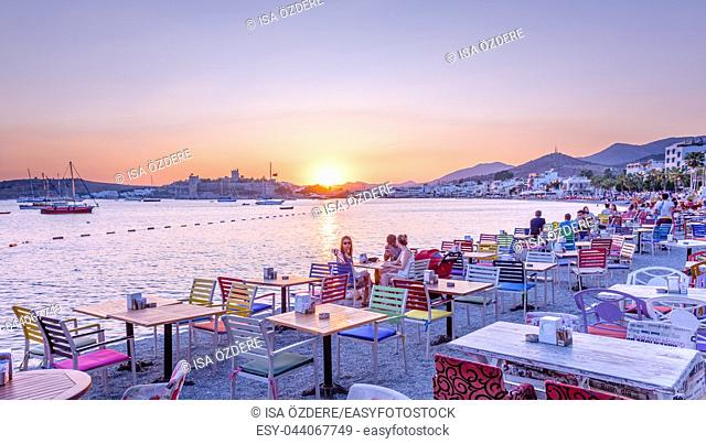 Unidentified people enjoy at beach cafe and Sunset view of Bodrum Marine with yachts and St. Peter Castle or Bodrum Castle view in Bodrum, Turkey