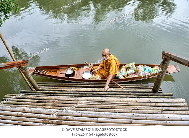 monk doing morning alms run by boat at the Amphawa Floating Market, Thailand