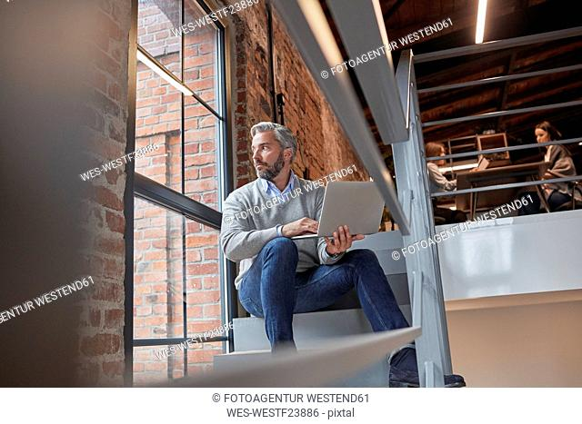 Businessman sitting on stairs of modern office, using laptop