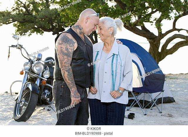 Mother and tattooed son camping at the beach
