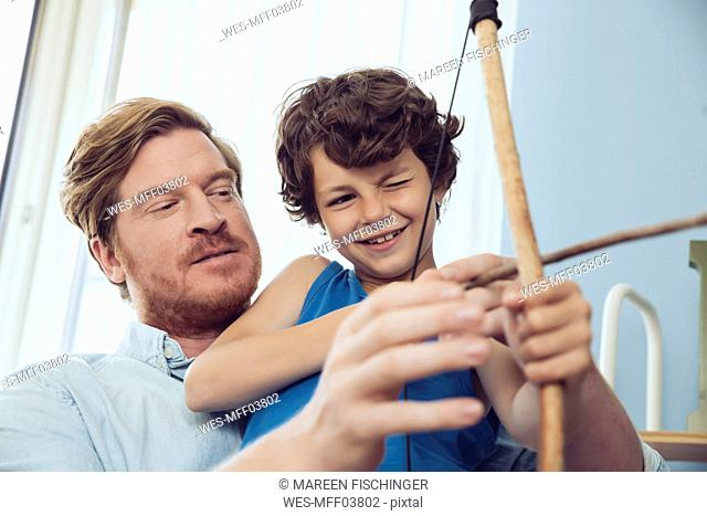 Father showing son how to use self-made bow and arrow