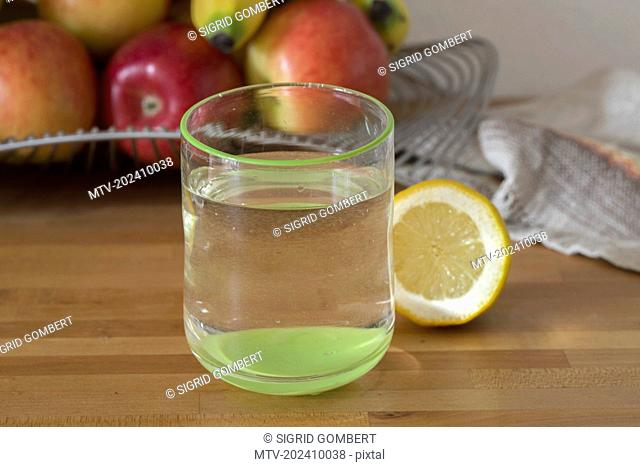 Close-up of lemon water with fruits in background