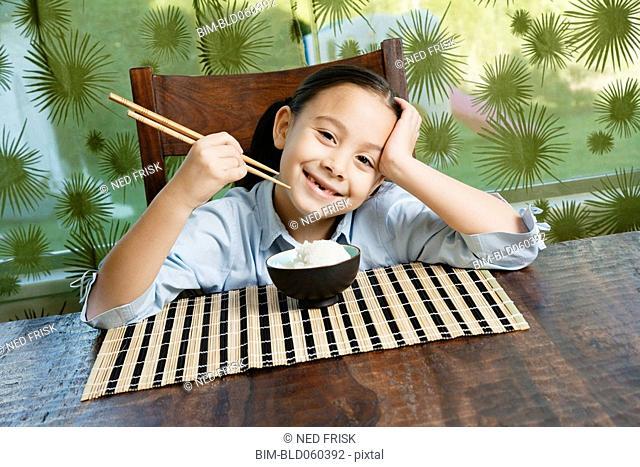 Asian girl eating bowl of rice