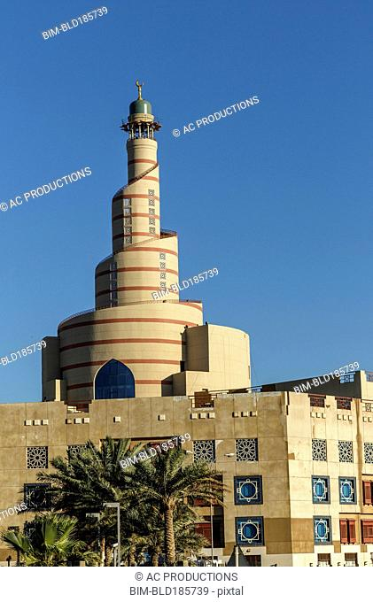 Islamic Cultural Center spire under blue sky, Doha, Qatar