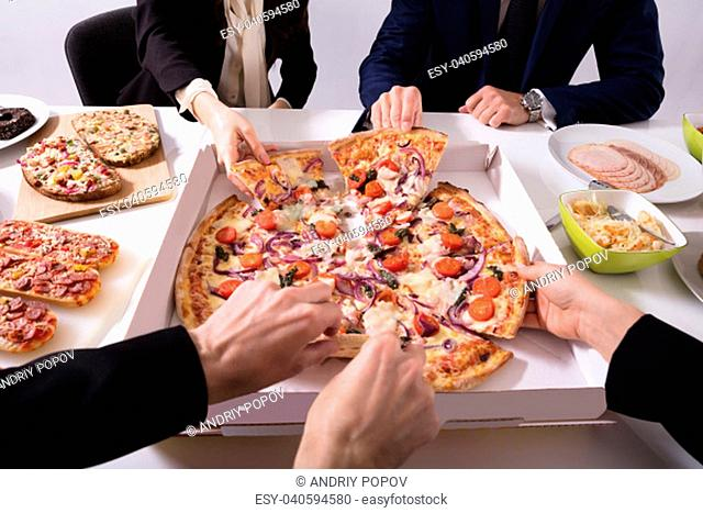 Friends Picking Slice Of Pizza From Box On Table