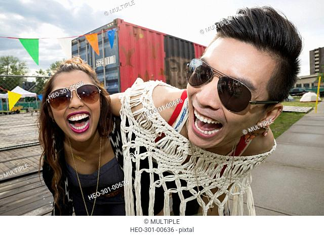 Portrait playful young couple with sunglasses laughing