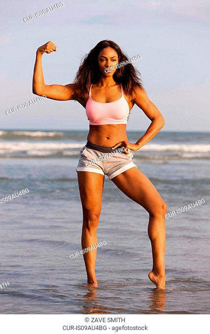Young woman on beach, flexing muscles, posing