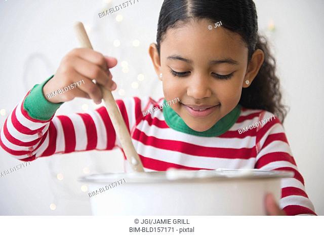 Close up of mixed race girl stirring dough