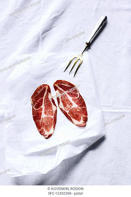 Two slices of cured meat with a meat fork on a sheet of paper