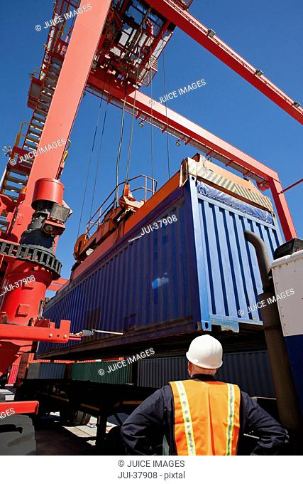 Worker watching crane load cargo container onto lorry at commercial dock