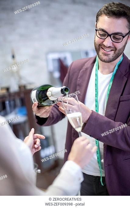 Fashion designer pouring champagne into glass