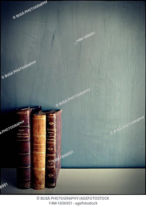 3 antique books on empty grey background