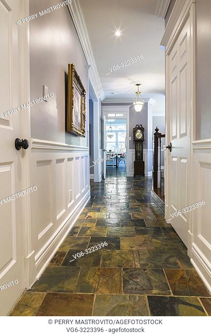 Ground floor hallway with earth tone slate flooring leading to the kitchen inside a contemporary cottage style home
