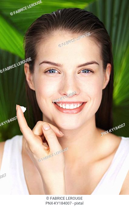 Portrait of young woman with sun cream on her finger