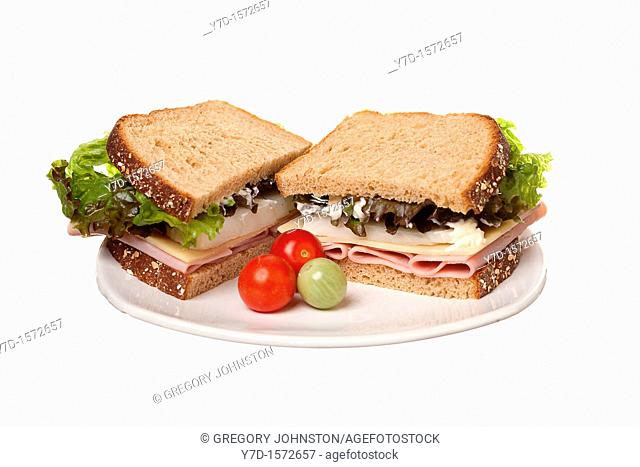 A ham sandwich loaded with cheese, onion, and lettuce on wheat and cherry tomatoes