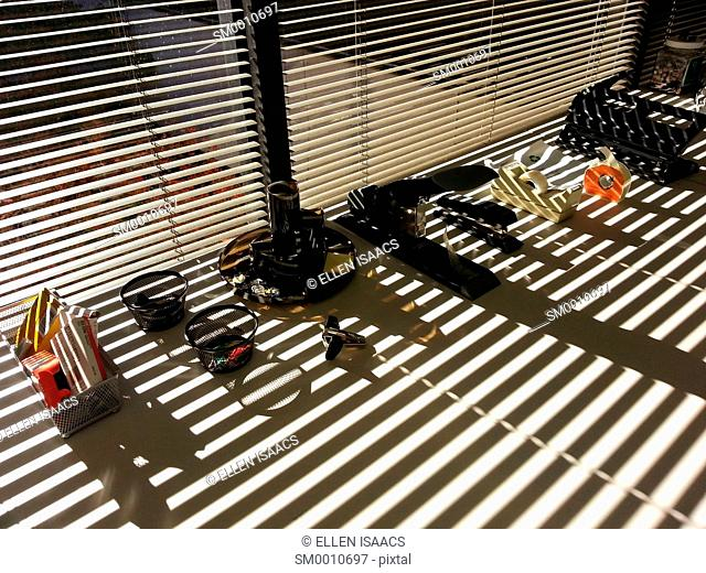 Office tools and office supplies lined up on a desk with Venetian blinds casting strong shadows across them in the afternoon