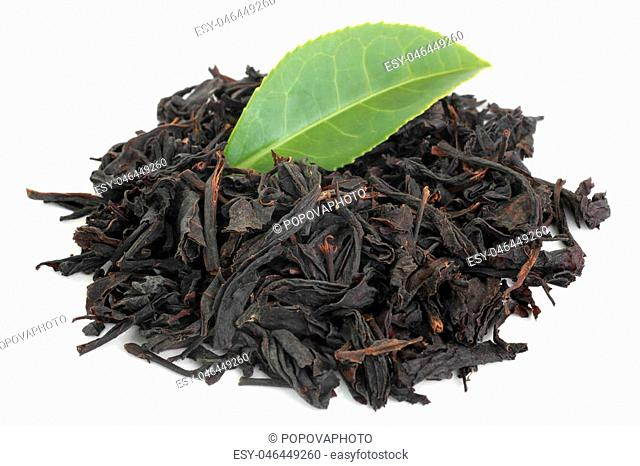 Black tea with green tea leaf on white background