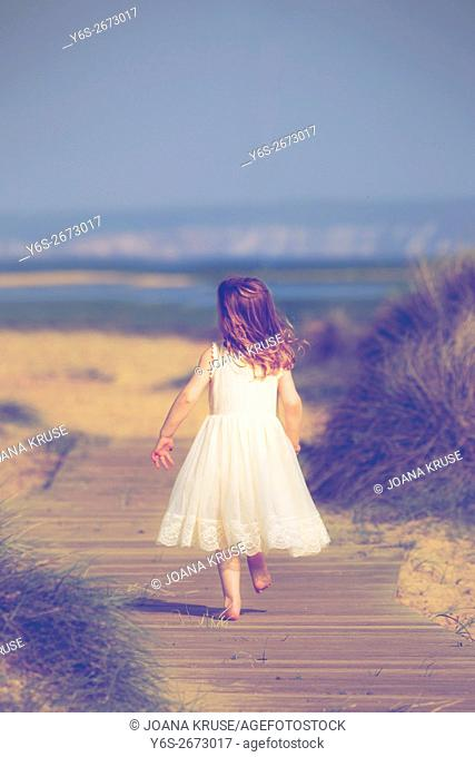 a 3 year old girl running on a boardwalk at the beach