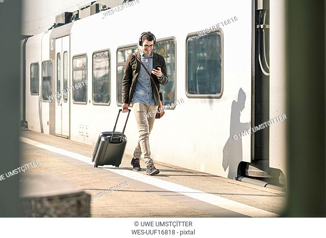 Smiling young man with headphones, cell phone and suitcase walking at station platform