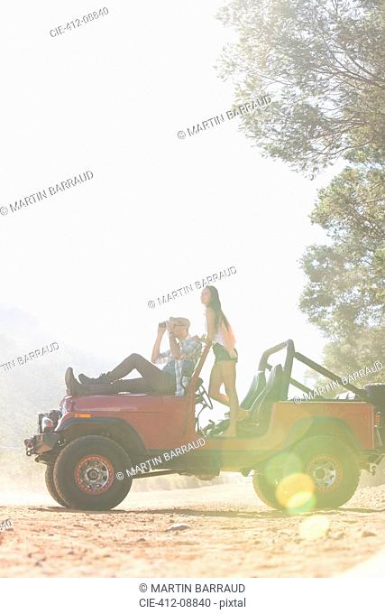 Couple relaxing in sport utility vehicle on dirt road