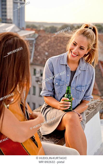 Young woman with girlfriend playing guitar at rooftop party