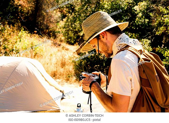 Man with camera by tent, Malibu Canyon, California, USA